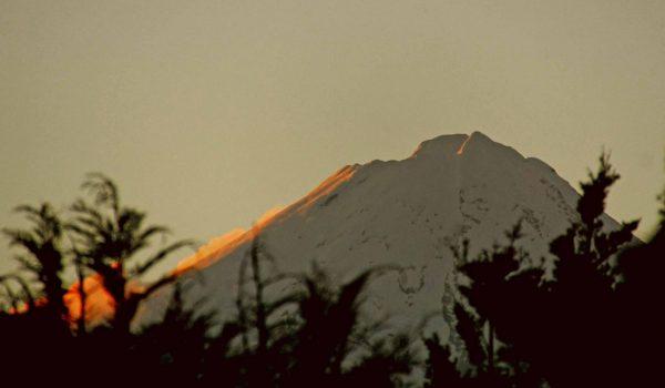 Der Mount Teranaki beschienen von der untergehenden Sonne.